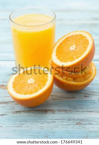 Glass of orange juice with fresh oranges - stock photo