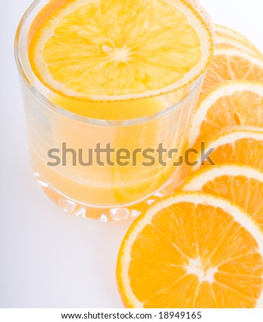 glass of orange juice with fruits near by