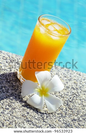 Glass of orange juice with ice against swimming pool. Shallow DOF. Vertical shot. - stock photo