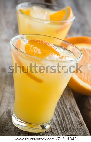 Glass of orange juice with ice cubes, selective focus - stock photo