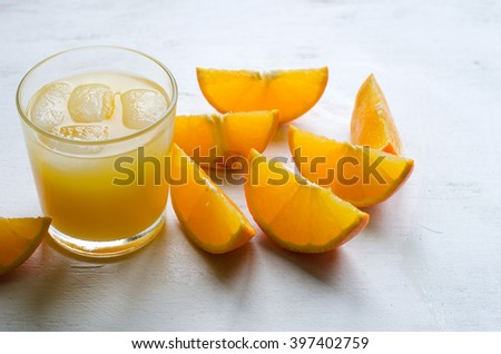 Glass of orange juice with ice on white background, selective focus