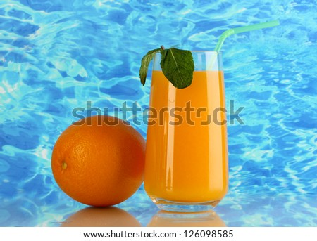 Glass of orange juice with mint and orange on sea background