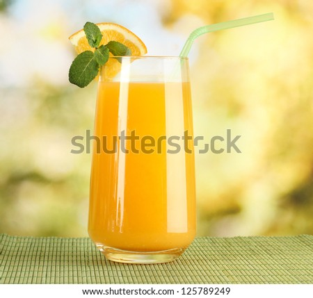 Glass of orange juice with mint on table on bright background - stock photo