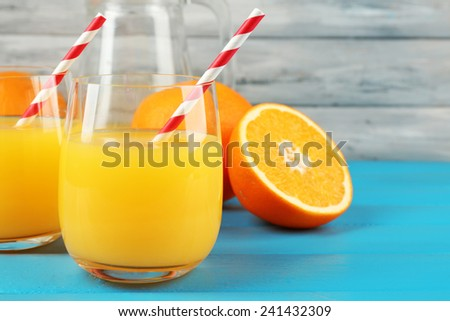Glass of orange juice with straws and slices on color wooden background