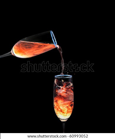 Glass of orange neon liquid pouring into another - stock photo