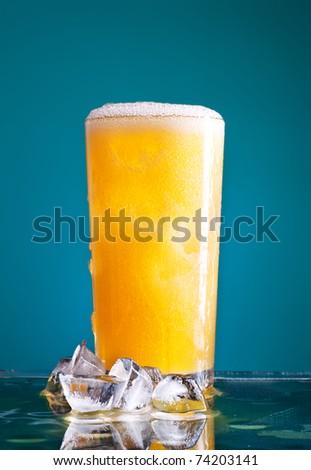 glass of orange soda with ice over blue background - stock photo