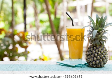 Glass of pineapple smoothie, juice and fresh fruit on a outdoor tropical background Copy space - stock photo