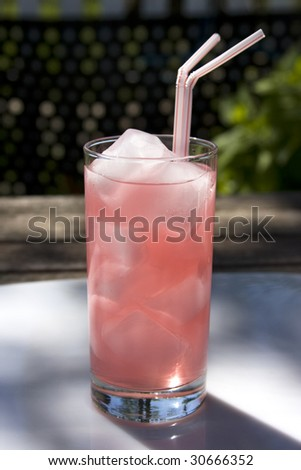 Glass of pink lemonade with ice and straws on a tray on top of a picnic table. - stock photo