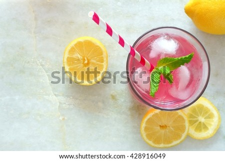 Glass of pink lemonade with mint and lemon slices overhead view on a white marble background - stock photo