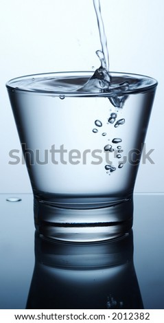 Glass of pouring water with reflection - stock photo