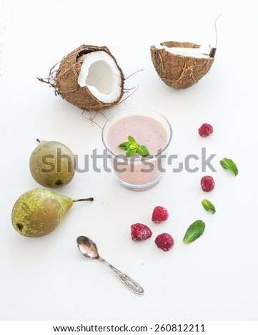Glass of raspberry, coconut, banana and pear smoothie with fresh mint leaves on white backdrop - stock photo