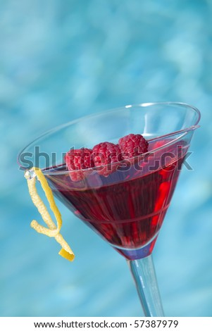 Glass of Raspberry Cosmopolitan cocktail on swimming pool side garnished with fresh raspberries - stock photo