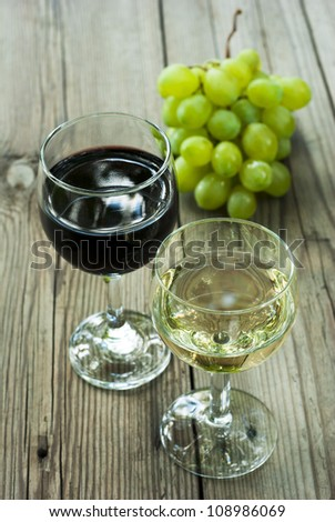 glass of red and white wine and cluster of grapes on wood table