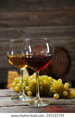 Glass of red and white wine, cheeses and grapes on grey wooden background