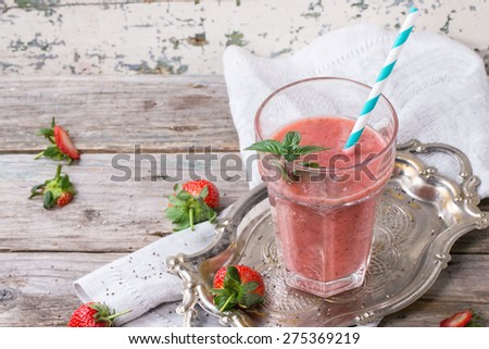 Glass of red strawberry smoothie with chia seeds, served with retro cocktail tube, fresh mint and strawberries over wooden table - stock photo