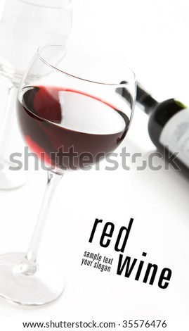Glass of red whine. Bottle in background. Photo taken in angle. - stock photo