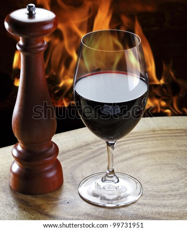 Glass of red wine and a fireplace in the background - stock photo