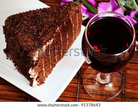 Glass of Red Wine and a Piece of Chocolate Cake - stock photo