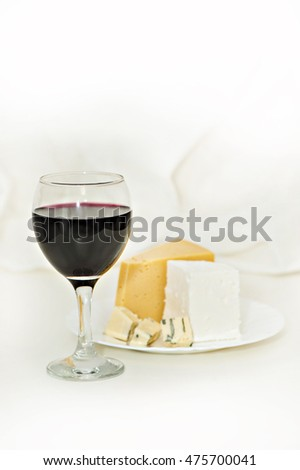 Glass of red wine and a plate of cheese