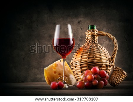 Glass of red wine and bottle braided on dark background - stock photo