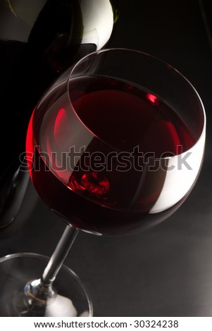Glass of red wine and bottle close-up on black background.