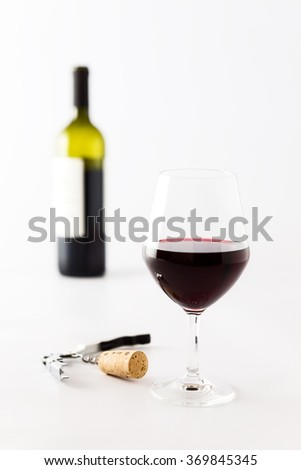 Glass of red wine and bottle, cork and corkscrew on a white background - stock photo