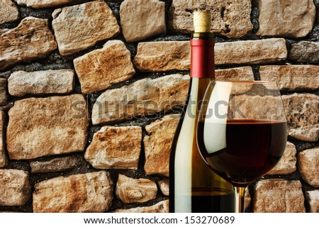 glass of red wine and bottle in a wine cellar near the stone wall - stock photo