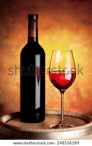 Glass of red wine and bottle on a wooden barrel - stock photo