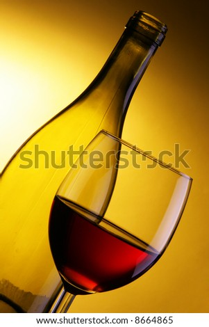 Glass of red wine and bottle over yellow background
