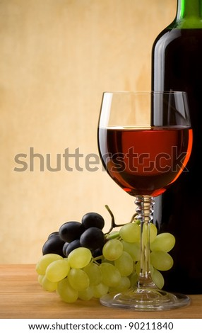 glass of red wine and bottle with grape on wood background - stock photo
