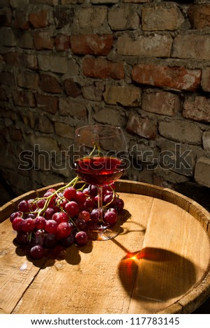 Glass of red wine and bunch of grapes - stock photo