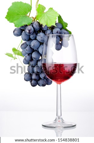 Glass of red wine and bunch of grapes with leaves isolated on a white background