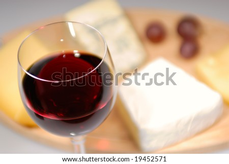 Glass of red wine and cheese plate - stock photo