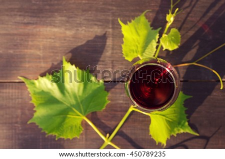 Glass of red wine and grape leaves on a wooden surface in beams of the setting sun
