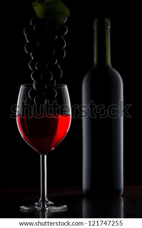 Glass of red wine and grape over black