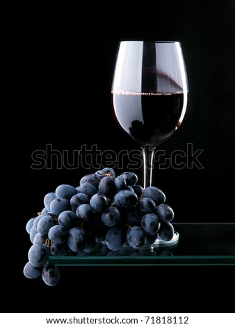Glass of red wine and grape over black - stock photo