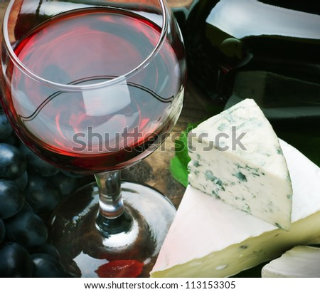 glass of red wine and grapes are ripe. Focus on a glass of wine - stock photo