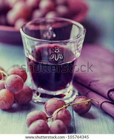 Glass of red wine and grapes on the table - stock photo