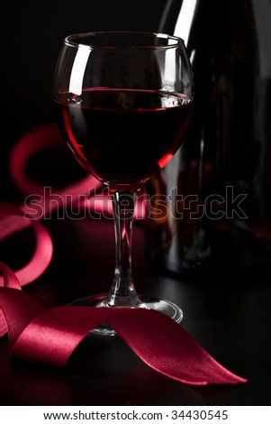 glass of red wine and red ribbon over black background - stock photo