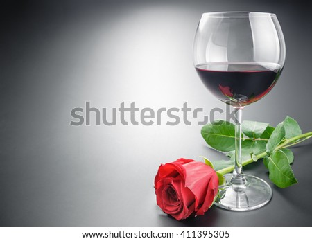 Glass of red wine and red rose flower arranged with some space on neutral gray gradient background. - stock photo