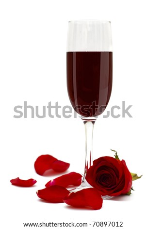 Glass of red wine and rose flower and petals - stock photo