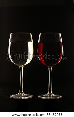 Glass of Red Wine and White Wine against Black Background - stock photo