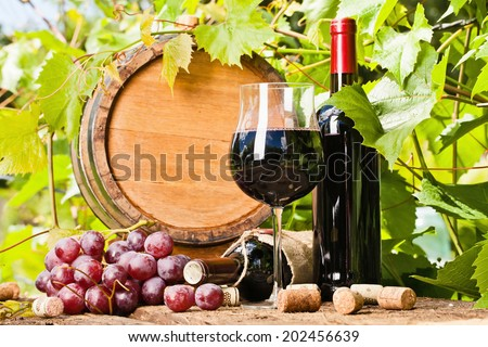 Glass of red wine, bottle and barrel on the background of grape leaves