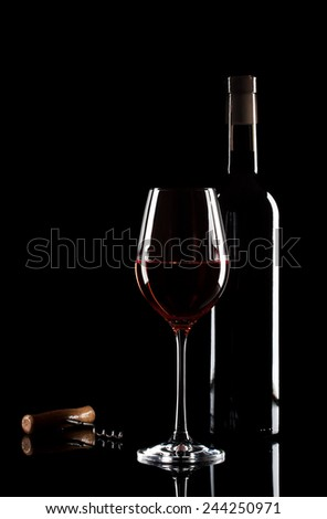 Glass of red wine, bottle and corkscrew on a black glass - stock photo