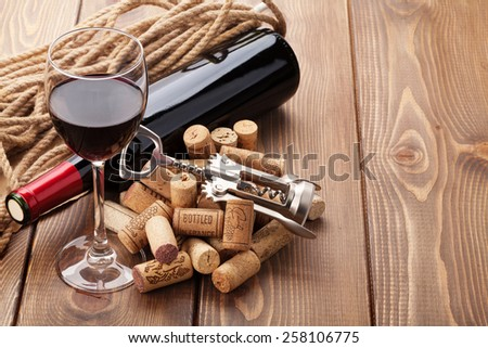 Glass of red wine, bottle and corkscrew on rustic wooden table with copy space - stock photo