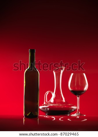 glass of red wine, bottle and decanter on red background