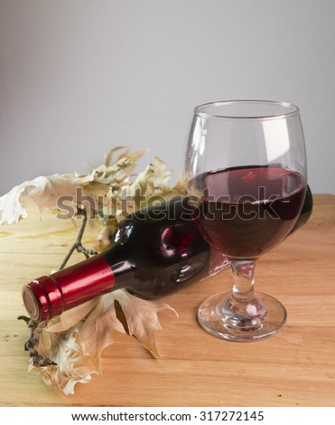 glass of red wine, bottle, dry autumn leaves, wooden background