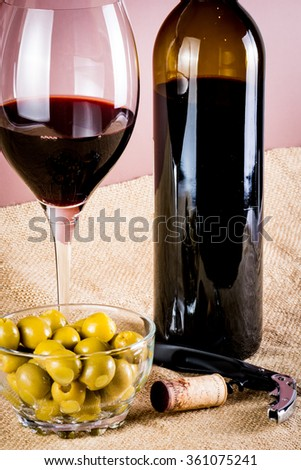 glass of red wine, bottle of wine, corkscrew and olives - stock photo