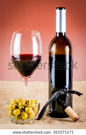 glass of red wine, bottle of wine, corkscrew and olives