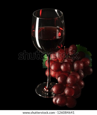 Glass of red wine, bunch of grape on black background.